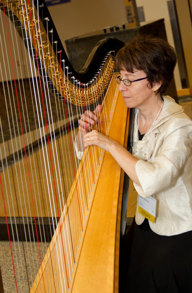 Diana Gumas, IT Director for JH SOM playing the harp