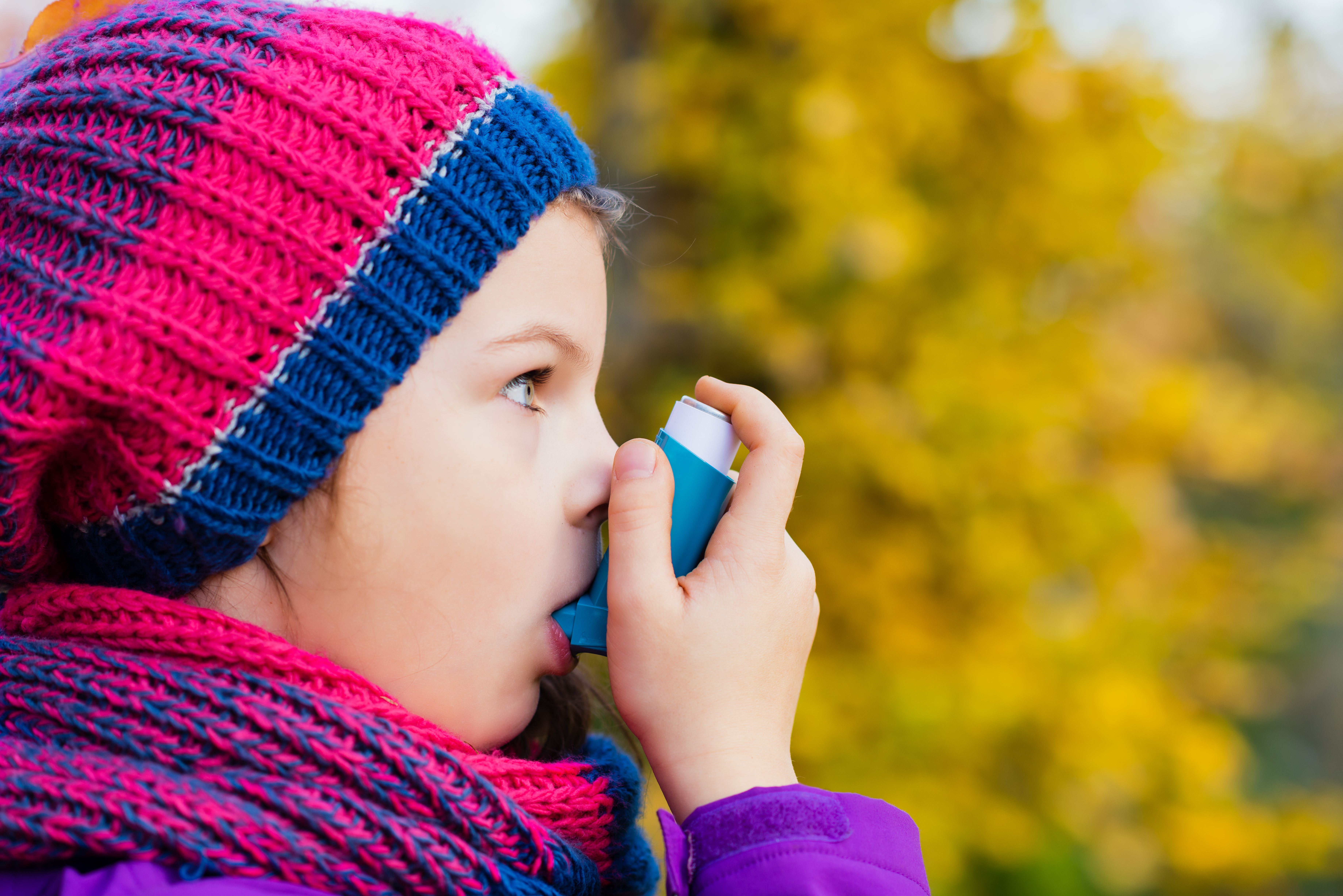 Girl Using Inhaler on a autumn day - to Treat Asthma Attack. Inhalation treatment of respiratory diseases. Shallow depth of field. Child Allergy Asthma concept.